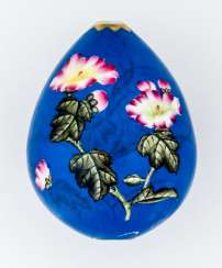 Large porcelain Easter egg with flowers on a blue Fond