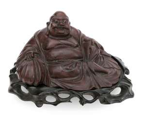 The wooden figure on his bag seated Budai