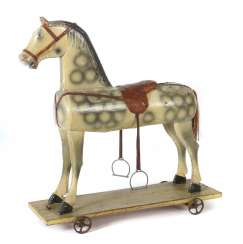 Wooden horse on wheels circa 1920, on a rolling-Board, mounted the horse, four-spoke metal wheels, in-mold optics, painted, saddle leather m