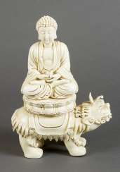 Blanc-de-Chine porcelain sculpture of Buddha sitting in lotus shaped seat, with a pot for the poor, on a fantastic animal