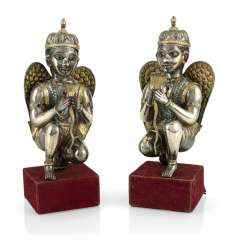Two silver figures with wings, partly gold-plated