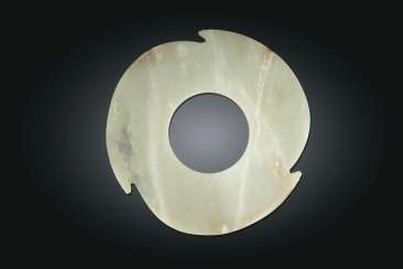 A RARE PALE GREEN JADE NOTCHED DISC