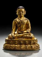 FIRE GILT BRONZE OF A SEATED LAMA