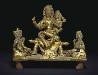 A GILT-COPPER GROUP OF SHIVA AND PARVATI WITH A DIVINE RETIN...
