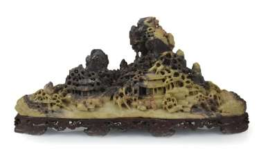 Soapstone carving of a house in the middle of a mountain landscape