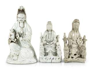 Three Dehua figures of Guanyin with boys and Adorants