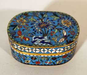 A small Chinese cloisonee oval box with lid, richly floral decorated in multicolours on blue ground, with white decoration band on the border
