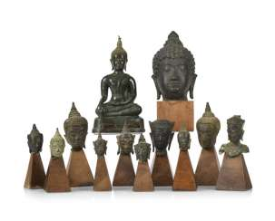 Eleven bronze heads and a bronze sculpture of the Buddha Shakyamuni