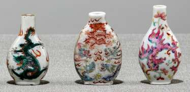 Three Snuffbottles made of porcelain with dragon - or Phoenix, decorated in polychrome enamel colors