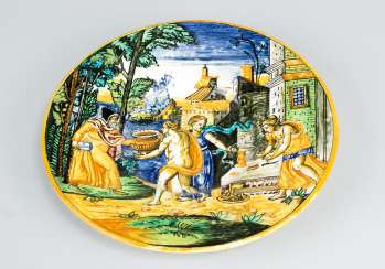 Urbino ceramic plate with bright round border and moulded center with multi colored paint of an allegorical scene in front of houses and the sea