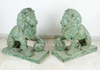 Pair of large bronze lions in sitting position with ball in paw on rectangular integrated bases