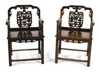 Pair of arm chairs made of hard wood with antique decor sit in the back