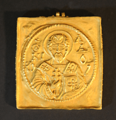 A gold amulet with two eyes and chased St. Nicholas with inscription