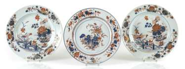 Three plates made of porcelain in the Imari style, decorated with Lotus and a garden scene